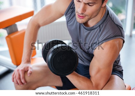 Closeup of attractive young man athlete sitting and exercising with dumbbell in gym