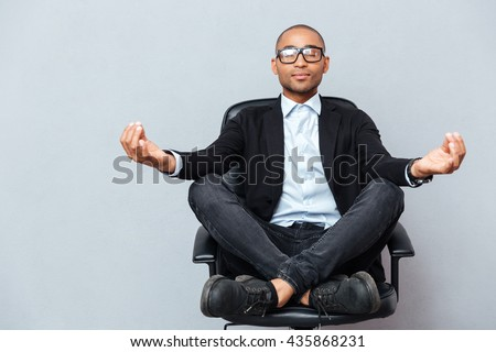 Closeup of attractive young man in glasses meditating on office chair - stock photo