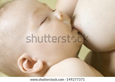 Closeup of baby boy breastfeeding - stock photo