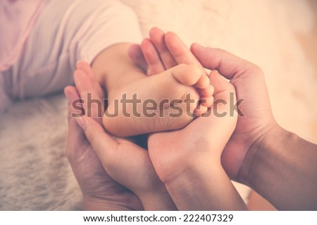 Closeup of baby feet into parents hands. Family concept Vintage colour - stock photo