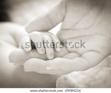 closeup of baby hand in back and white - stock photo