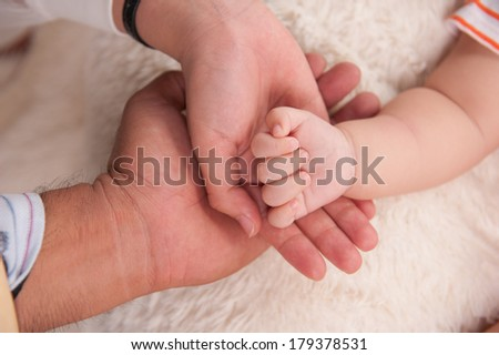 Closeup of baby hand into mother and father hands. Family concept