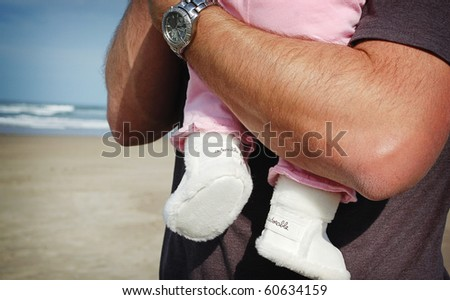 Closeup of Baby in Adorable Boots at the Beach in Daddy's Arms - stock photo