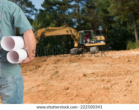 closeup of back view of standing engineer holding plans on outdoors constrution site - stock photo