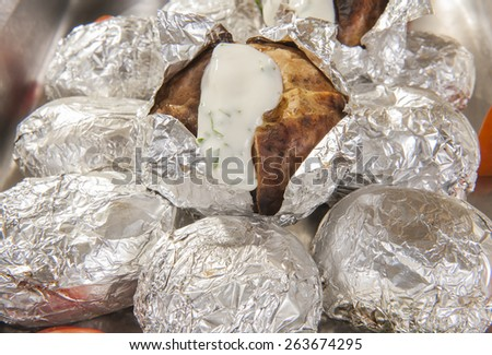 Closeup of baked jacket potatoes in silver metal foil with white sauce at a hotel restaurant buffet - stock photo