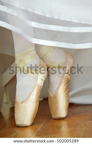 Closeup of  ballerina's legs with ballet shoes and a white dress.