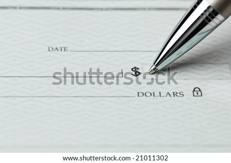 Closeup of ballpoint pen writing on a blank bank check, ready to fill in the dollar amount; selective focus on the tip of the pen - stock photo