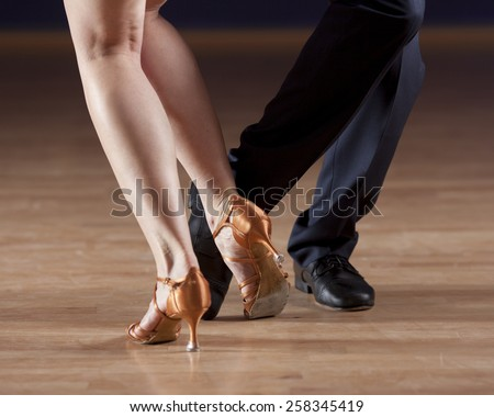 closeup of ballroom dancers legs in studio setting - stock photo