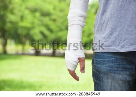 closeup of bandaged arm  with park background - stock photo