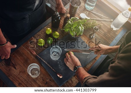 Closeup of bartenders hands cutting lemons to prepare at cocktail. Two barmen experimenting with new recipes for cocktails at the bar counter. - stock photo