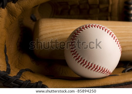 Closeup of baseball and baseball bat in glove with warm lighting.