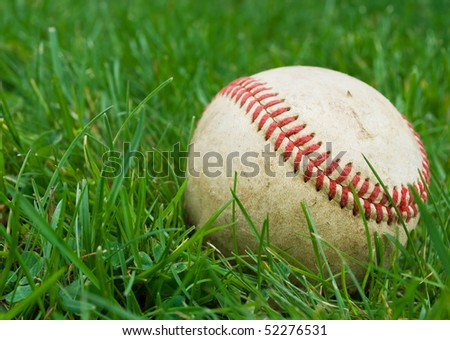closeup of baseball in the grass, shallow depth of field with focus on ball - stock photo