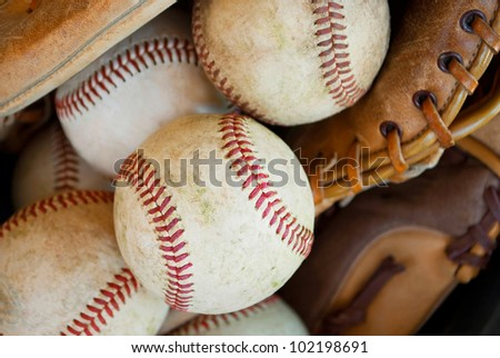 closeup of baseballs and leather glove used for baseball practice - stock photo