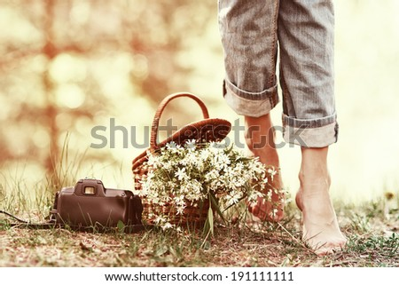 Closeup of basket with white flowers, camera and female legs barefoot in jeans - stock photo