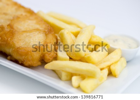 Closeup of battered fish and chips with tartar sauce on white - stock photo