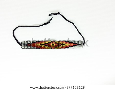 Closeup of beaded native american bracelet with red, orange, yellow and black beads on white background and taken against white background.