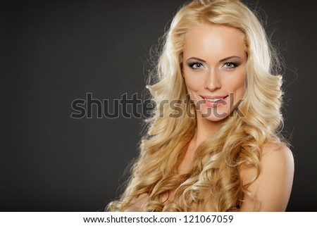 Closeup of beautiful blond female with  beautiful hair, over dark background - stock photo