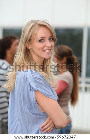 Closeup of beautiful blond woman with arms crossed - stock photo