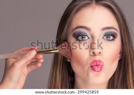 closeup of beautiful blond young woman getting makeup done in cheeks - stock photo