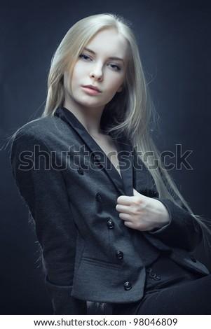 closeup of beautiful blonde woman in coat on dark background - stock photo