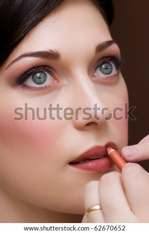 closeup of beautiful brunette young lady prepared for the event by makeup artist - stock photo