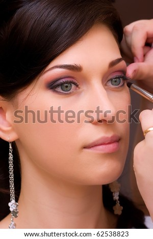 closeup of beautiful brunette young lady profile prepared for the event by makeup artist - stock photo