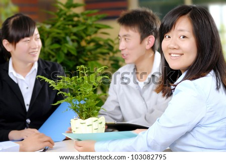 Closeup of beautiful business woman with colleagues discussing in background