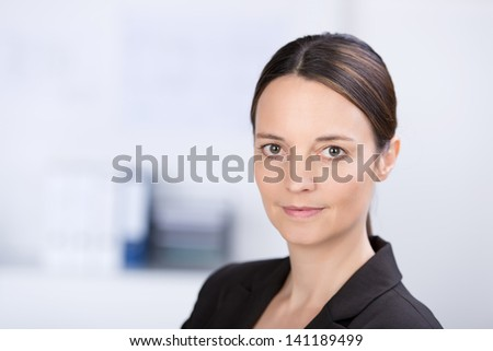 Closeup of beautiful businesswoman looking in camera in her office - stock photo