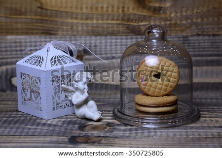 Closeup of beautiful cupid angel decorative figurine near white paper greeting valentine box and red hanging clothes-peg with round cookie under glass flask on wooden background, horizontal picture - stock photo