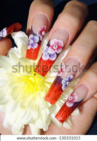 closeup of beautiful 3D flower see through crystal glass nail art design manicure holding a flower - stock photo