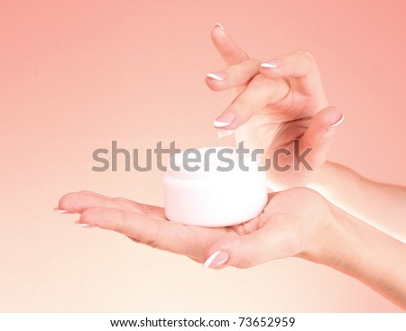 Closeup of beautiful female hands applying hand cream  on red background - stock photo