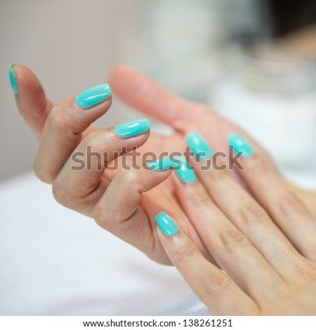 closeup of beautiful female hands with blue manicure on nails. - stock photo