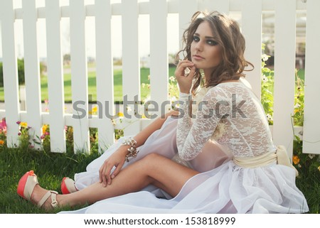 closeup of beautiful girl with dark makeup in long white dress outdoors. Exclusive beige and white dress. high heels - stock photo