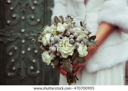 Closeup of beautiful green pastel wedding bouquet held by a bride in fur coat