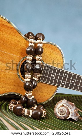 Closeup of beautiful Hawaiian koa wood ukulele with abalone inlay, on a palm frond draped with kukuinut lei, and a seashell on blue backgound - stock photo