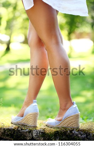 Closeup of beautiful legs in shoes of a woman walking in park - stock photo