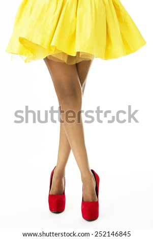Closeup of Beautiful Legs of African Model, Wearing Yellow Skirt and Red Shoes - stock photo
