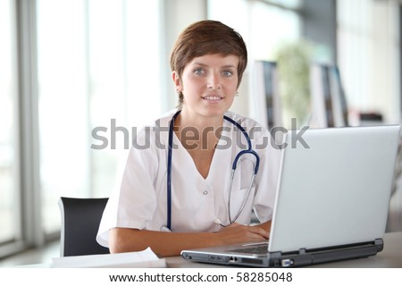 Closeup of beautiful nurse in front of laptop computer