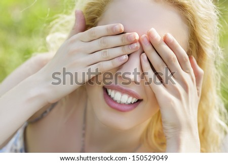 Closeup of beautiful playful smiling woman covering her eyes with both her hands. Hide-and-seek. - stock photo
