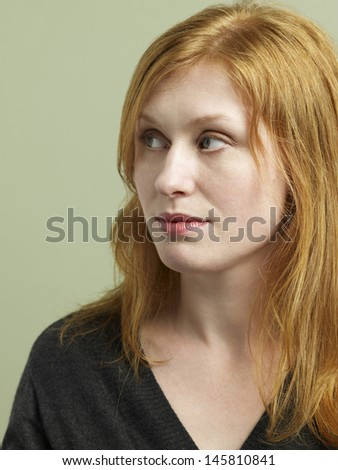 Closeup of beautiful red haired woman looking away on colored background