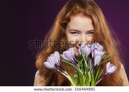 Closeup of beautiful redheaded female smelling the crocuses - stock photo