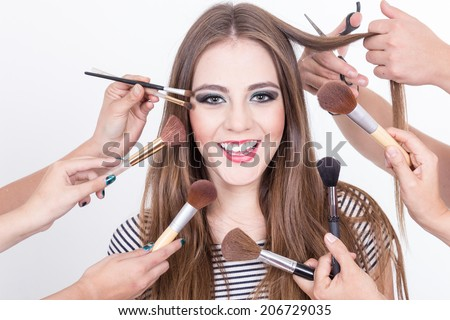closeup of beautiful smiling blond girl getting makeup done by many hands isolated over white