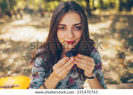 Closeup of beautiful teenage girl holding a tartatel with berries outdoors. Cute hipster brunette young woman on autumn day - stock photo