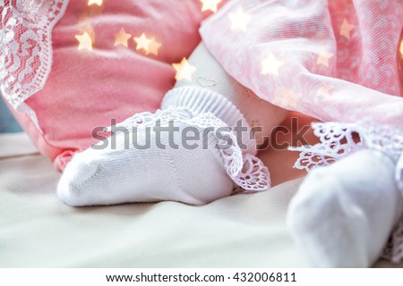 Closeup of beautiful white sock in the heart on the leg wearing newborn baby. Happy baby childhood. Background, macro.