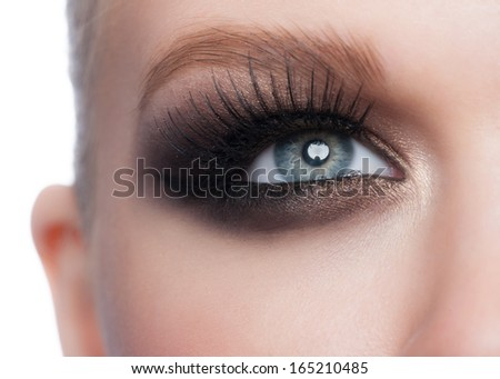Closeup of beautiful woman blue eye with bright stylish makeup with long lashes - stock photo