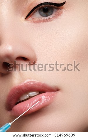 Closeup of beautiful woman gets injection in her lips. Full lips. Beautiful face and the syringe (plastic surgery and cosmetic injection concept).
