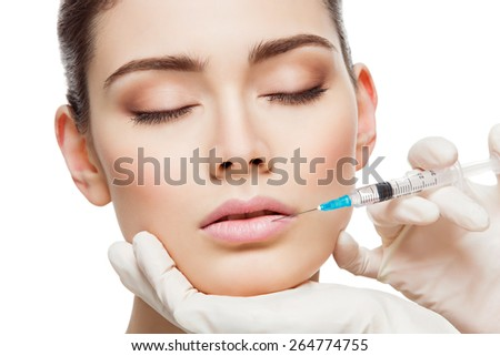 Closeup of beautiful woman gets injection in her lips. Isolated over white background