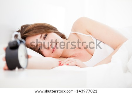 Closeup of beautiful woman lying on the bed with alarm clock - stock photo