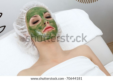 Closeup of beautiful woman, resting with clay mask on her face. - stock photo