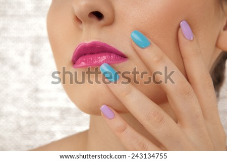Closeup of beautiful woman's lips and hand with colorful manicure - stock photo